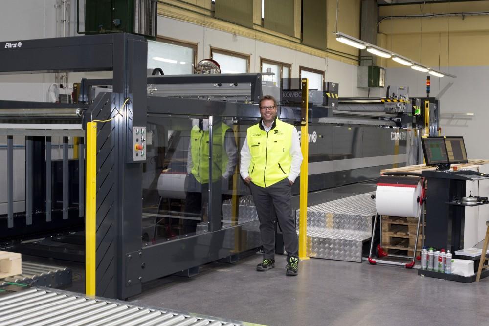 DS Smithin toimitusjohtaja Karri Koskelan takana näkyvä täysautomatisoitu Elitron-leikkuulinja voi valmistaa peräkkäin useita töitä, jotka se tunnistaa automaattisesti, leikkaa ja pinoaa lopuksi työt lavalle linjan toisessa päässä.