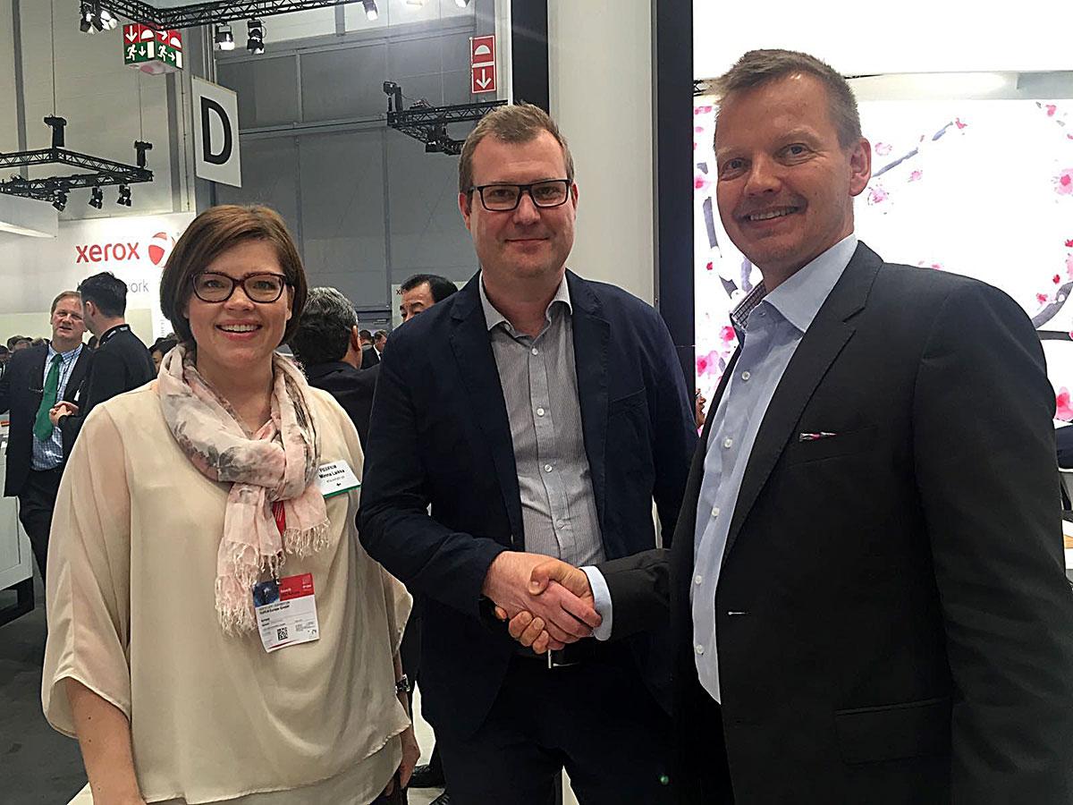 KTA-Yhtiöiden Minna Laikka, Hostmann-Steinberg Suomi Oy:n Rami Aalto ja KTA:n Voitto Savolainen löivät Drupa-messuilla kättä päälle.